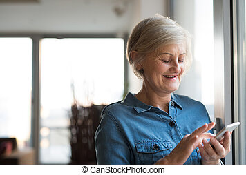 Senior woman with smartphone at home standing at the window...