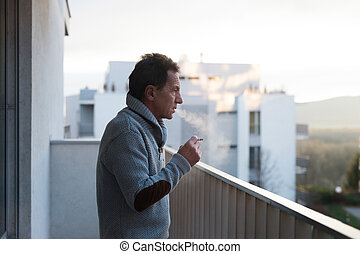 Serious senior man standing on balcony, smoking a cigarette...