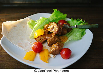 Seitan on white plate with the vegetables