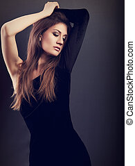 Sexy slim model posing in black dress on dark grey background and looking sexy with arms above the head. Toned fashion portrait