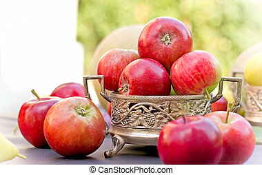Red apples in antique bowl on table