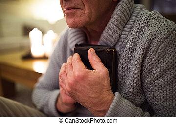 Senior man praying, holding Bible, burning candles behind...