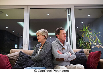 Offended senior couple sitting on a couch with arms crossed...