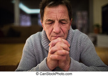 Senior man at home praying, hands clasped together - Senior...