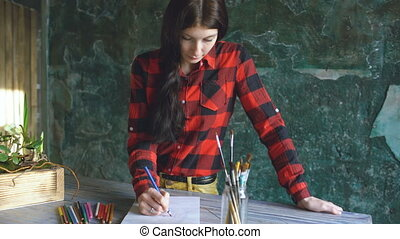 Young woman artist painting scetch on paper notebook with pencil