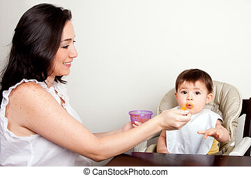 Funny baby messy eater - Beautiful happy mother or nanny...