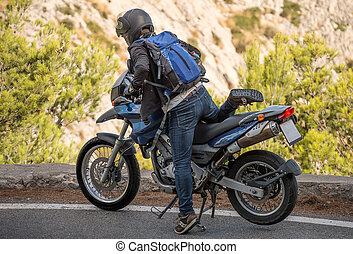 Tourist using motorcycle in mountains.