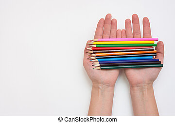 Female hand holding in his hands a dozen pencils, hands...