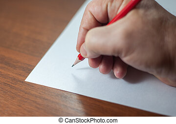 A close photo of a persons writing a letter with a pencil