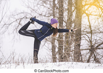 woman practices yoga in the winter - beautiful woman doing...