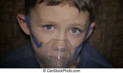 The boy is breathing through the inhaler.Full hd video
