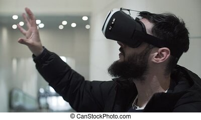Young Man using virtual reality goggles in shopping center