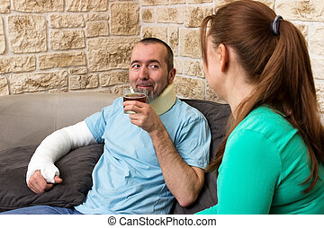 Nursing at home - A man with a broken arm drinking a tea