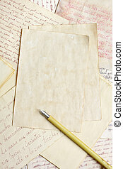 Aged empty paper sheets with vintage nib pen over antique...