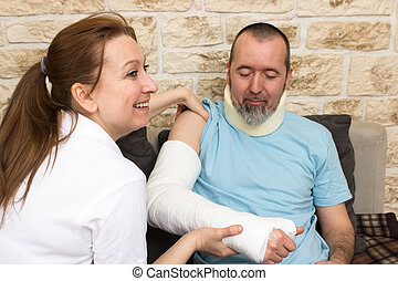 Friendly carer - A nurse smiles while examining an injured...