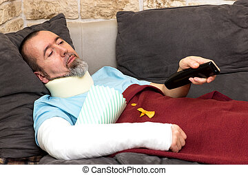 Bored injured man - Injured man lies on the couch and...