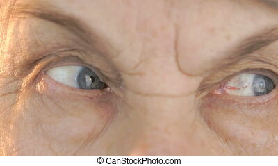 Senior woman opening and closing eyes. Close up