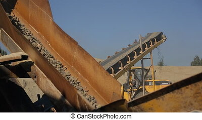 At the factory the yellow conveyor moves down coarse gravel....