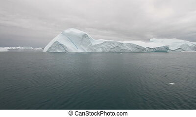 Sailing by an iceberg in the famous Ilulissat icefjord in...