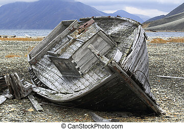 forgotten old boat - desert black beach with old boats run...