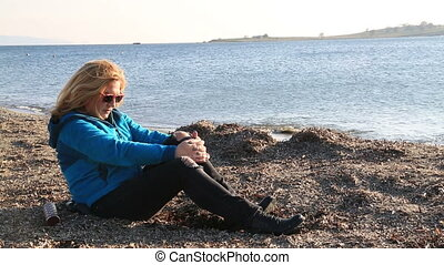 Sad woman sitting at the seaside - Thoughtful, pensive woman...