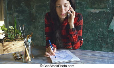 Young woman artist painting scetch on paper notebook with...