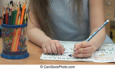 Little girl draws images in notebook using pencils