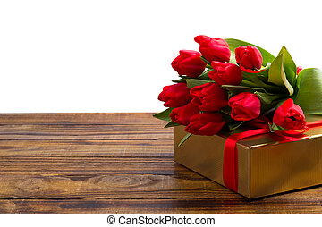 bouquet of red tulips and gift box on rustic wooden...