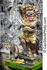 Statue - A statue in the temple and a cat eating sacrifices...