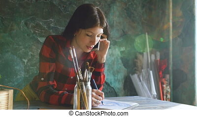 Young woman artist painting scetch on paper notebook with pencil. Girl smile and talks phone