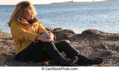 Woman in warm clothing sitting on winter beach - Portrait of...