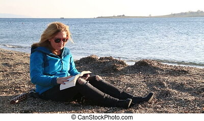 Woman reading a book at the seaside - Middle aged woman...