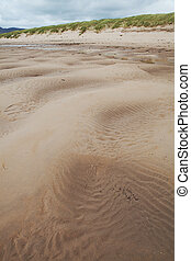 patterns in sand and water at beach with copy space