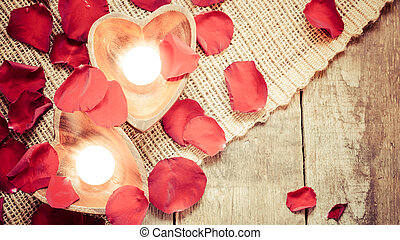 Two enlightened candles in heart-shaped candleholders with...