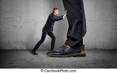 Little businessman is pushing a big boss's huge feet on gray background
