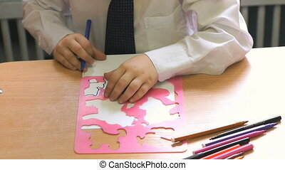 Child draws the image using the markers. Close-up - Child...