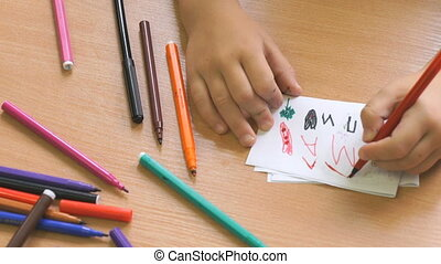 Kid draws the image using the felt pens. Close-up - Kid...