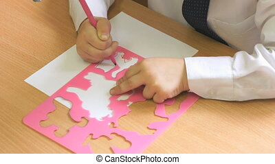 Kid draws the image using a felt pen. Close-up - Kid sitting...
