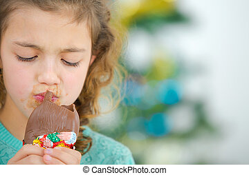Greedy little girl eating chocolate