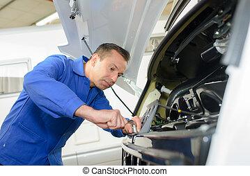 Mechanic working on front of motor caravan