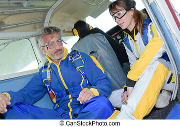 Man and woman wearing jumpsuits in aircraft
