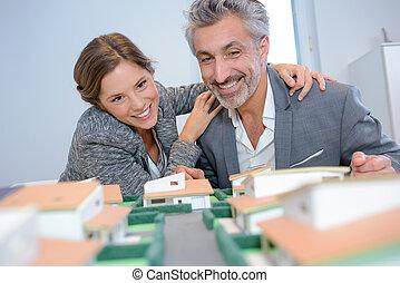 Man and woman joyfully looking at model housing development