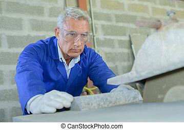 mason making granite gravestone