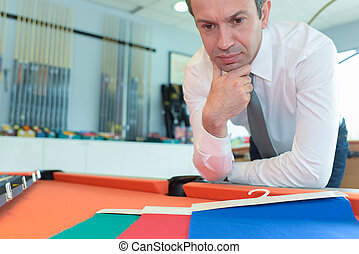 Man pondering color scheme for pool table