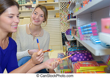Women looking at pens in stationery shop
