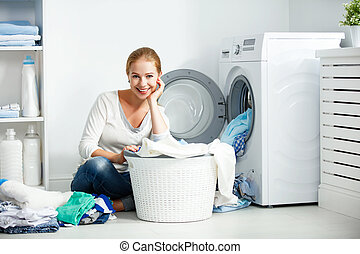 happy woman housewife in the laundry room near the washing...