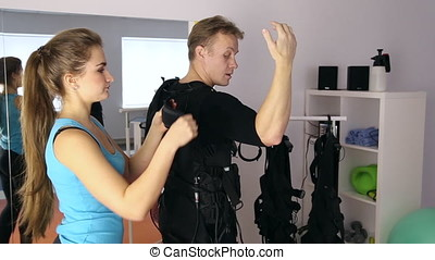 Personal ems training in the gym, trainer puts ems training...
