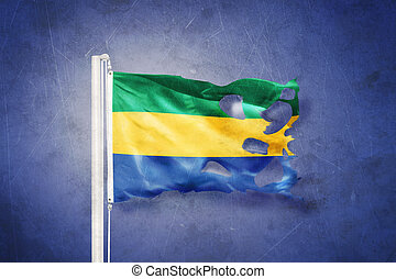 Torn flag of Gabon flying against grunge background.
