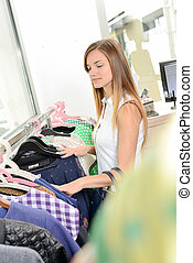 Girl looking through rail of clothes