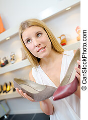 Undecided lady holding two shoes